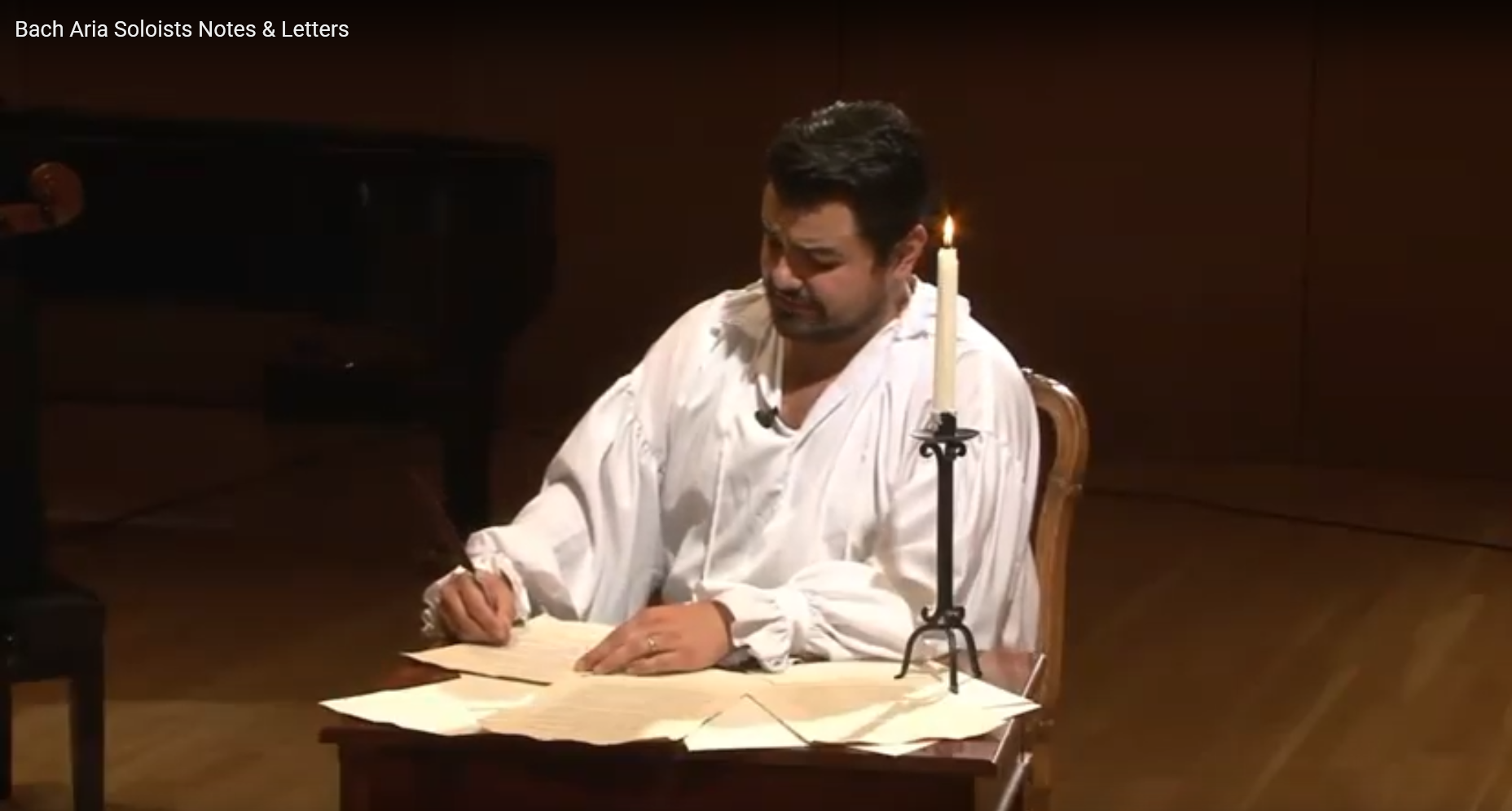 Man in white shirt at desk with letters and candle.