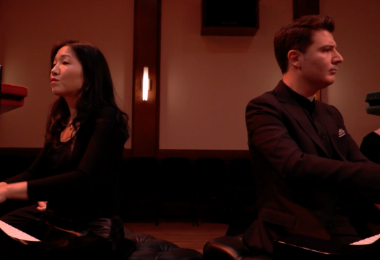 A woman and man play duo pianos.