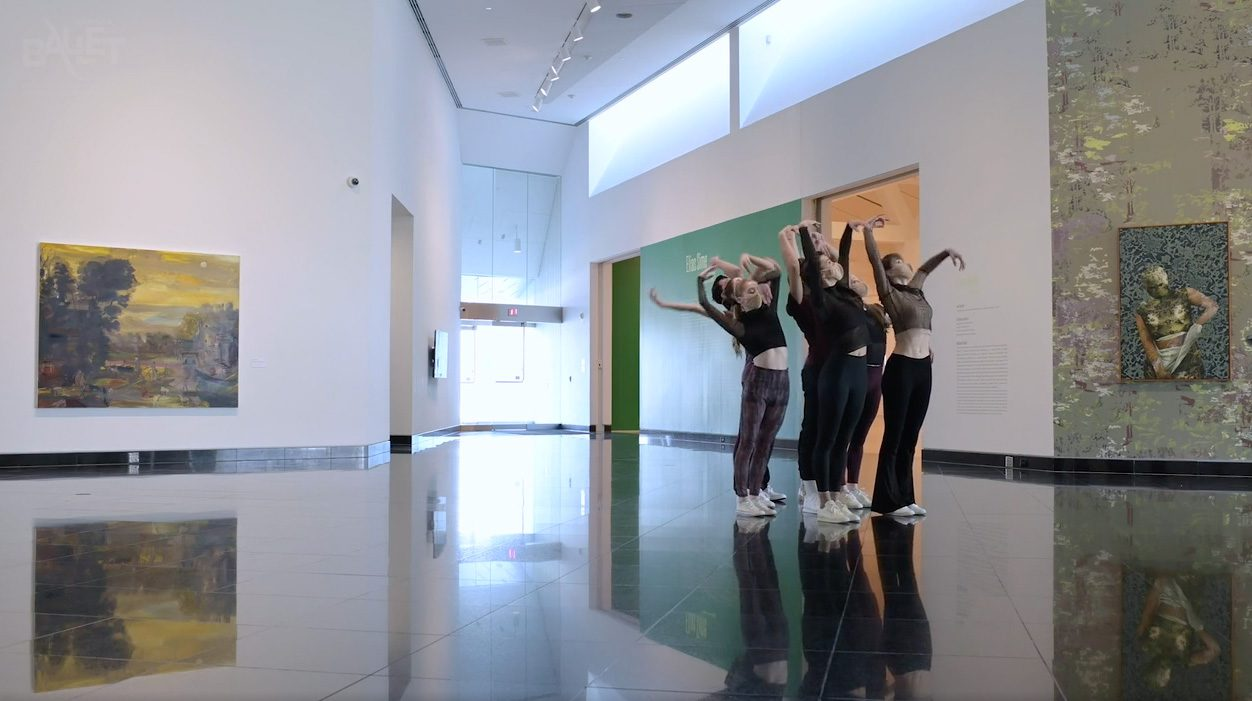 Dancers raise their arms in the lobby of a modern art museum.