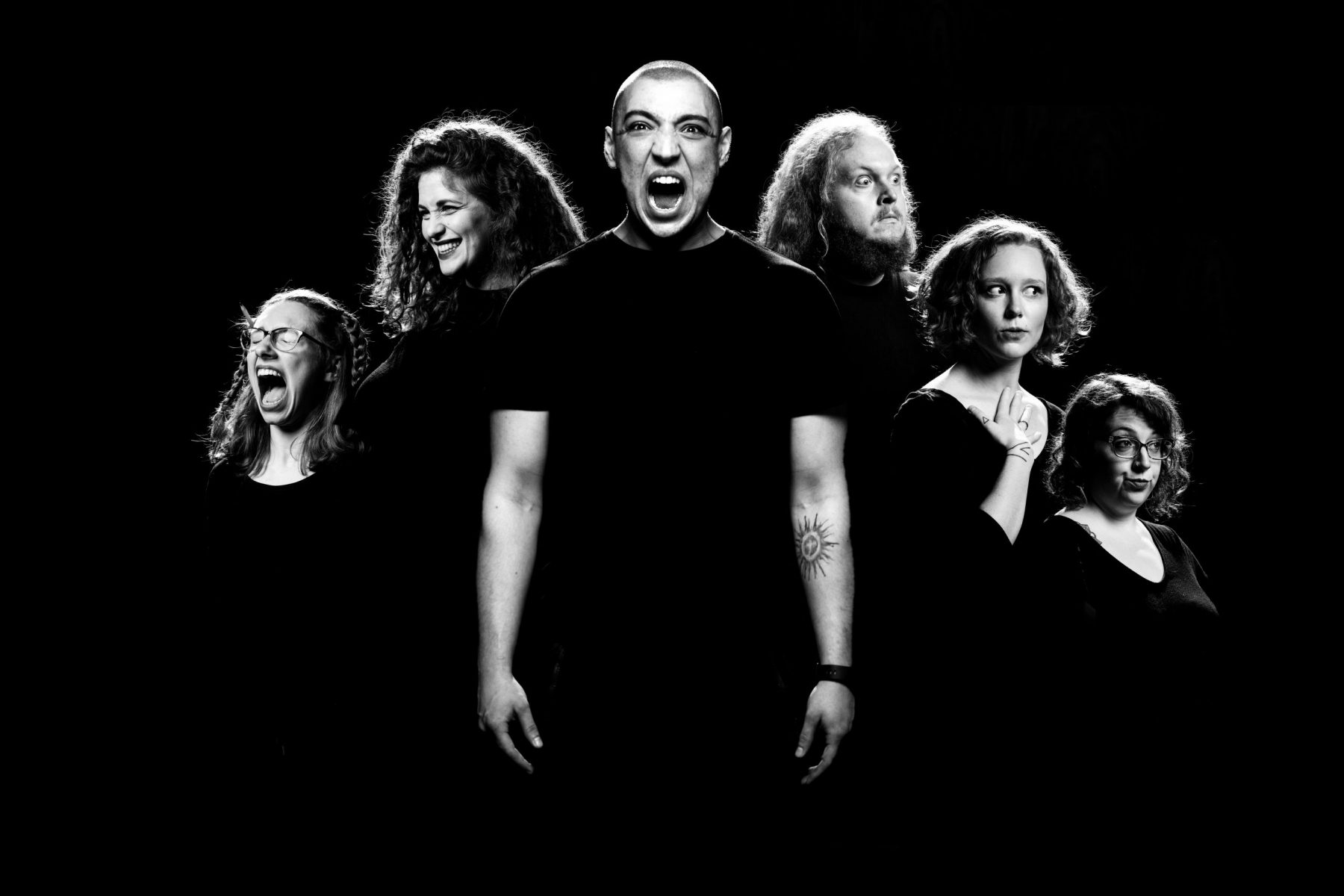 Six people making exaggerated facial expressions, in black and white.