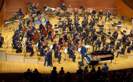 An orchestra behind two men, a father and son, hugging.